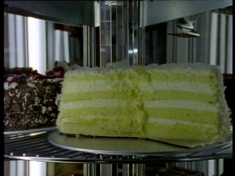 a variety of cakes rotate around a disco mirrored display cabinet. - display cabinet stock videos & royalty-free footage