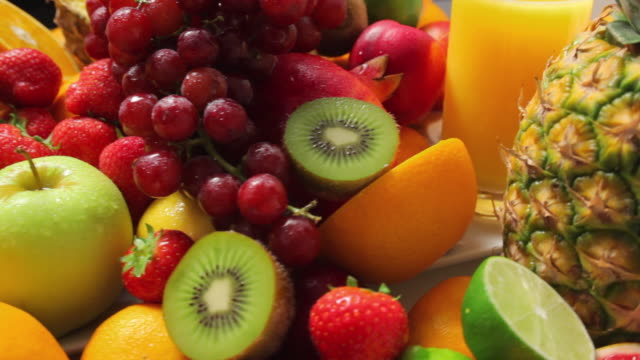 cu variety of fruits and glass of fresh juice / london, united kingdom - inquadratura dall'alto di un tavolo video stock e b–roll