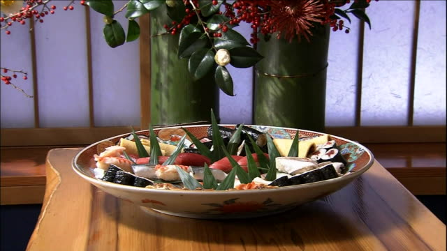 a variety of nigiri ovals arranged on a platter lie on a counter top beside flowers arranged in a bamboo vase. - nigiri stock videos and b-roll footage