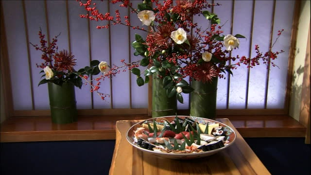 a variety of nigiri ovals arranged on a platter lie on a counter top beside flowers arranged in a bamboo vase - nigiri stock videos and b-roll footage