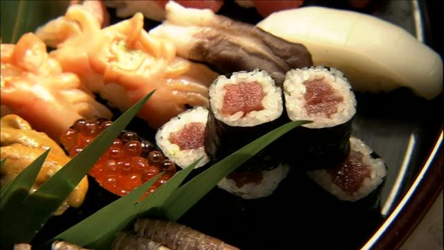 a variety of nigiri-sushi covers a tray. - nigiri stock videos and b-roll footage