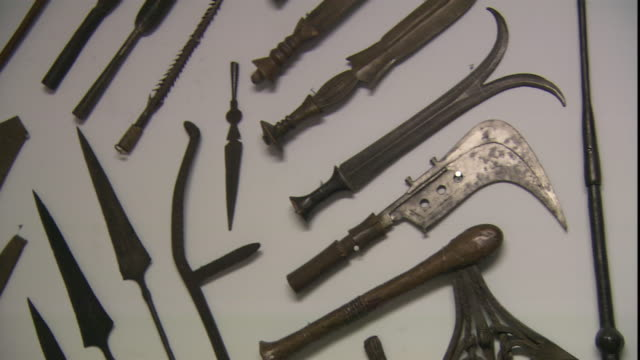 a variety of primitive weapons hang on a wall for display. - dagger stock videos & royalty-free footage