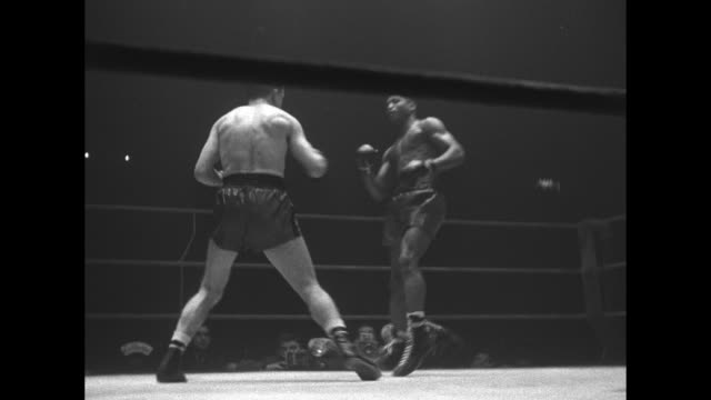 various action shots from fight between africanamerican boxer norman hayes and french boxer charles humez at palais des sports / fight ends and both... - ボクシングリング点の映像素材/bロール