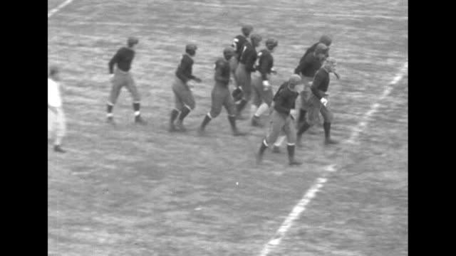 various action shots from football game / people walking across field after game / note: exact year not known; documentation incomplete - torschuss stock-videos und b-roll-filmmaterial