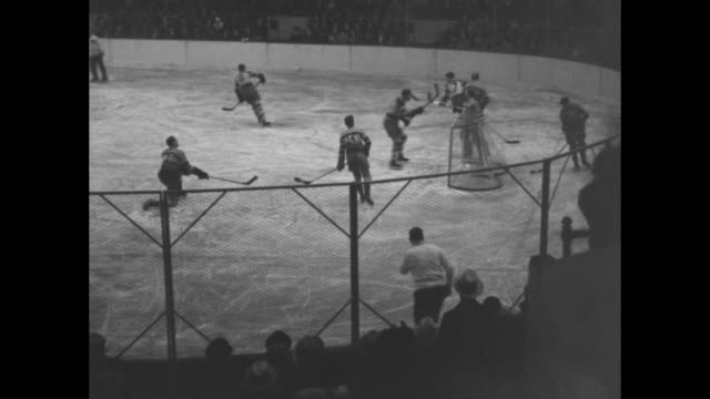 Various action shots from game between Boston Bruins and the New York Americans at Madison Square Garden with spectators standing on occasion to...