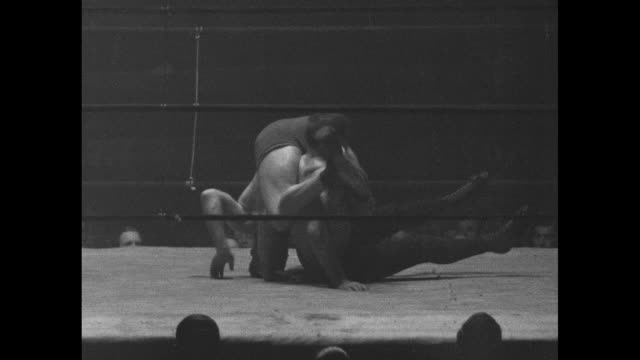 Various action shots from wrestling match between Dick Shikat and Jim McMillen including one shot of both men falling out of ring / Note exact...