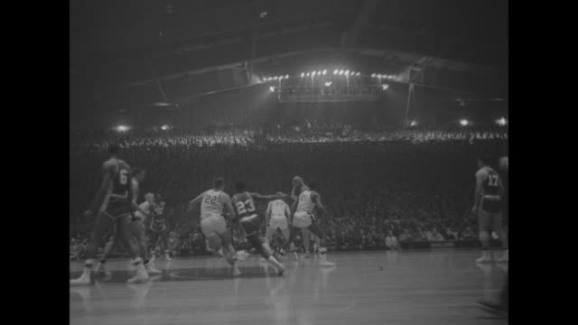 Various action shots of basketball game between San Francisco Dons with star player Bill Russell and Iowa Hawkeyes interspersed with shots of crowd...