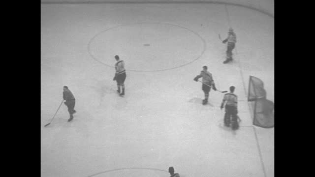 Various action shots of game between Montreal Canadiens and Boston Bruins in Centre Bell arena interspersed with shot of spectators and shot of game...