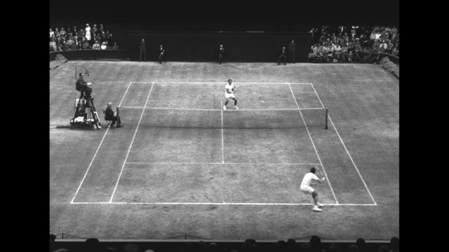 Various action shots of Tony Trabert of US playing tennis championship match against Kurt Nielsen of Denmark at Wimbledon one shot of crowd...