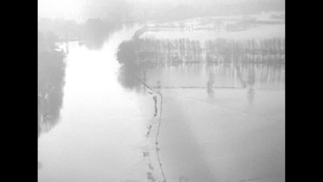 Various aerial shots of flooding of Thames River including shots of Windsor Castle surrounded by flood waters / Note exact day not known