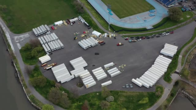 vídeos de stock e filmes b-roll de various aerial shots of refrigerated trucks which are prepared to be used by hospitals as makeshift morgues for coronavirus victims, arrive near to... - morte