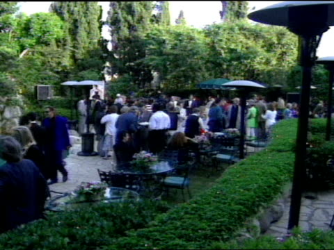 WS various angles crowd of guest standing outdoors at Playboy Mansion near pool HA across pool LA across pool HA over hedges and picnic tables