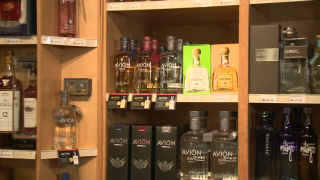 stockvideo's en b-roll-footage met various angles of avion tequila bottles on display in a liquor store - avion