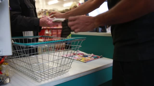 Various anonymous shots an employee serves customers at the checkout counter scanning goods putting cash into till handing change back placing...