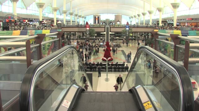 stockvideo's en b-roll-footage met various areas in denver international airport with long security lines and people walking through the airport checking flights during the holiday... - dia