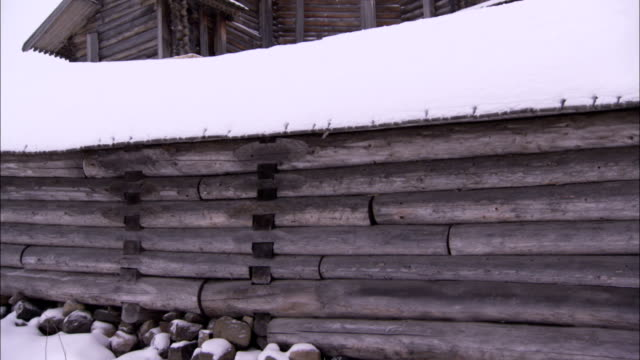 various atmospheric shots of a snow covered graveyard with traditional wooden grave markers sticking out of the snow - daytime. available in hd. - bbc点の映像素材/bロール