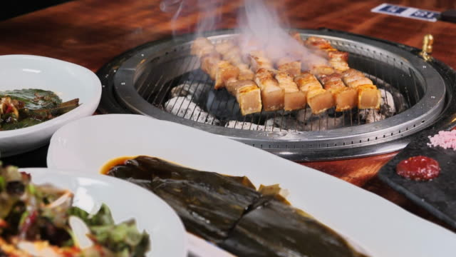 various 'banchan' and grilled 'samgyeopsal' (pork belly) - 韓国文化点の映像素材/bロール