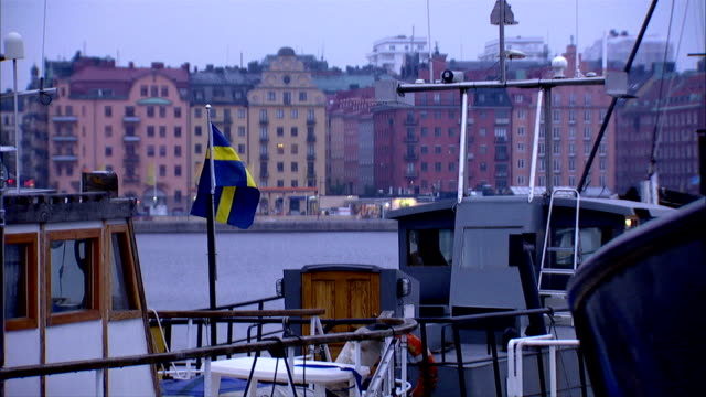 various boats docked at bay flag of sweden flying on small pole on boat buildings along riddarfjarden bay bg scandinavia quay wharf scandinavian... - swedish flag stock videos and b-roll footage