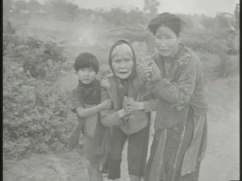 various chinese refugees walking through war torn town collapsed buildings bg family w/ emaciated elderly female walking another elderly slouched on... - ausgemergelt stock-videos und b-roll-filmmaterial
