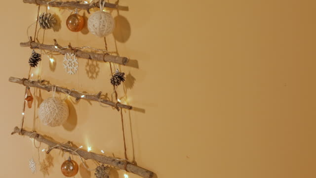 stockvideo's en b-roll-footage met various christmas ornaments hanging on the wall - dennenappel