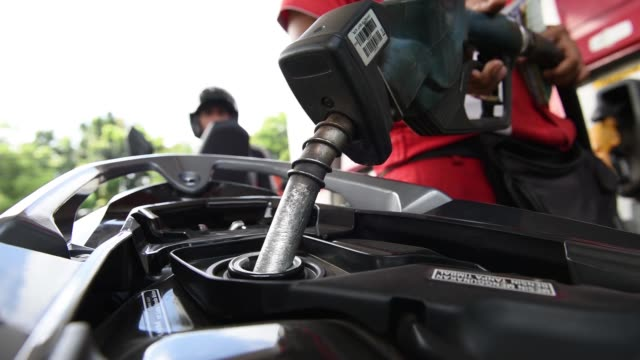 various close up views of gas pump nozzle as an attendant refuels a customers motorcycle at a pt pertamina gas station in jakarta indonesia on... - gas station attendant stock videos and b-roll footage