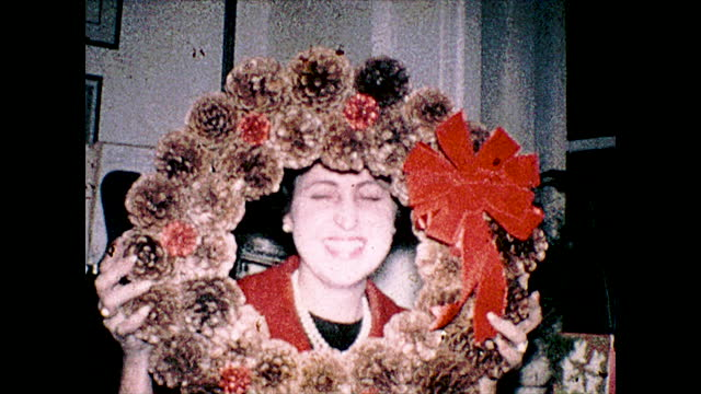 various close up views of people smiling and posing with a holiday wreath made of pine cones with a red ribbon; people gathered for a group photo;... - employee engagement stock videos & royalty-free footage