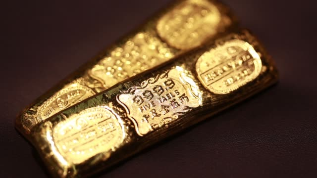 vidéos et rushes de various close up views of two 5tael gold bars displayed inside a chow sang sang holdings international ltd jewelry store in the mong kok district of... - mong kok