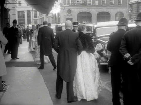 stockvideo's en b-roll-footage met various dignitaries arrive at the royal opera house for the gala premiere of benjamin britten's new opera - gloriana. 1953. - winterjas