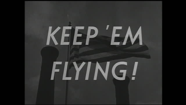 "various explosions during battle and tanks surrounded by soldiers firing; american flag flying between two smokestacks; title card: ""keep 'em flying!"" - 1940 1949 video stock e b–roll"