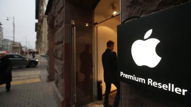 Store premium Apple Inc reseller customers entering and exiting signage branding in Moscow Russia on Wednesday Nov 12 A customer browses products on...