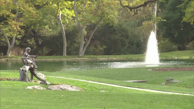 various exterior scenic shots of the neverland ranch property grounds in los olivos, california, a wide shot of a pond with a fountain in the middle... - ネバーランドバレーランチ点の映像素材/bロール