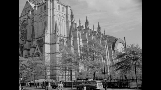 pans cathedral front from towers to sidewalk / crowd enters cathedral doors up stairs / queen mother between dr grayson kirk, columbia university... - kathedrale stock-videos und b-roll-filmmaterial