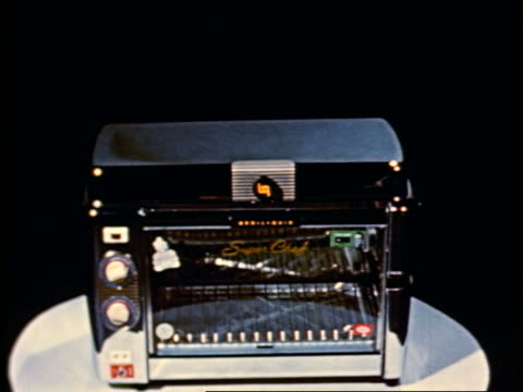 1950 stop-motion various foods appearing in large oven that converts to griddle + rotisserie - gruppo di oggetti video stock e b–roll