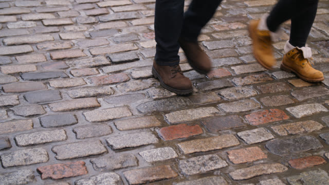 ms of various footwear on cobbled road - kopfsteinpflaster stock-videos und b-roll-filmmaterial