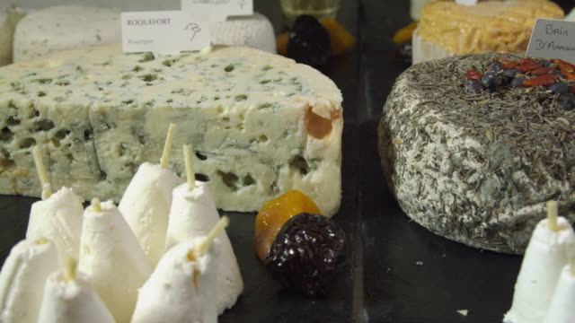 ecu pan various french cheeses arranged on cheese board - french culture stock videos and b-roll footage