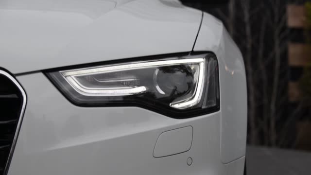 various front views from lightemitting diodes illuminating a headlight of an audi ag a5 cabriolet vehicle - fanale anteriore video stock e b–roll