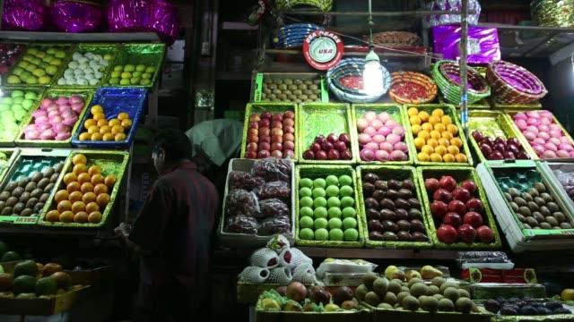 stockvideo's en b-roll-footage met various fruits on display at fruit stalls inside crawford market in mumbai india on thursday dec 5 a vendor arranges his display of mandarins oranges... - for sale korte frase