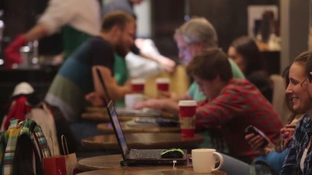 Various general views filmed through windows of customers using their laptop computers and smartphone devices at tables inside coffeeshops in Moscow...
