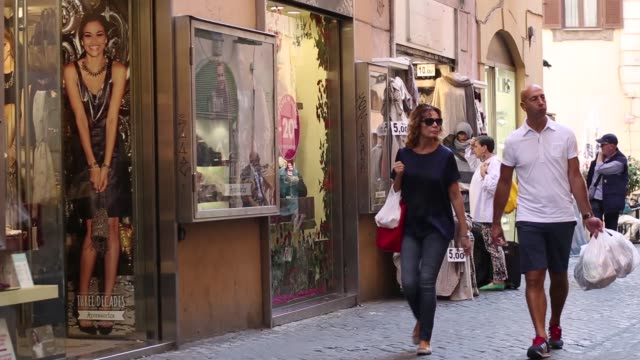 vídeos de stock, filmes e b-roll de various general views pedestrians walk along pedestrianised shopping streets and browse goods displayed outside clothing stores in rome italy on... - produto interno bruto