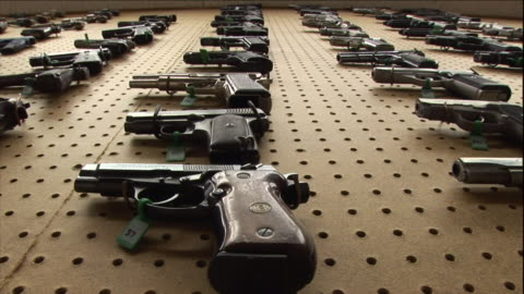 various handguns hang on a board in a forensics lab. - handgun stock videos & royalty-free footage