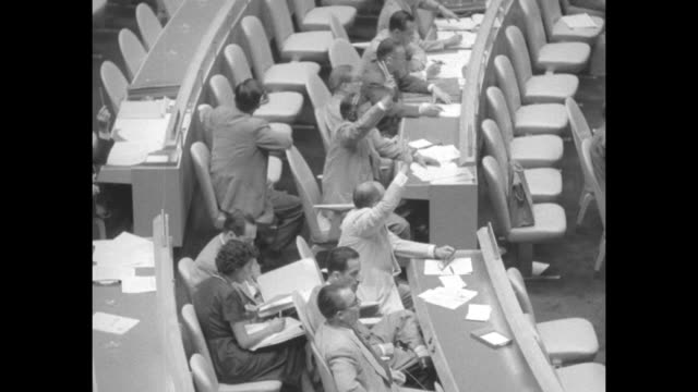 various high angle shots looking down on delegates voting by raising hands / united kingdom delegate voting / delegates; one raises hand / delegates;... - united nations general assembly stock videos & royalty-free footage