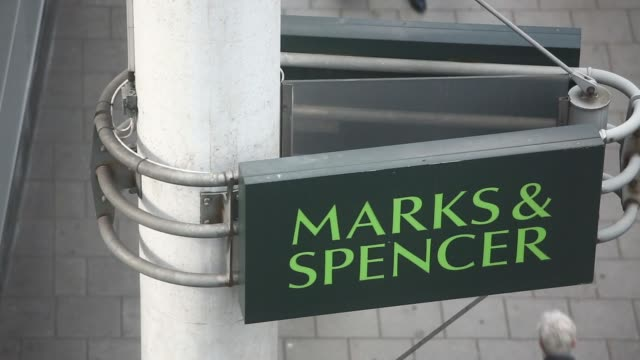 Various high angle shots pedestrians walk past a Marks Spencer retail store operated by Marks Spencer Group Plc in London UK on Tuesday May 20 Pull...