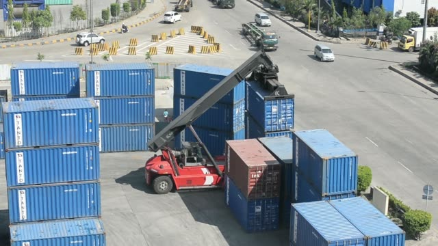various high angle views a kalmar reachstacker transports shipping containers from freight trucks to the dockside at the tanjung priok port operated... - newly industrialized country stock videos and b-roll footage