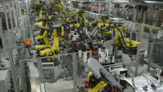 Various high angle views robots work on Seat Leon vehicles on the production line during assembly at Volkswagen AGs Seat automobile plant in...