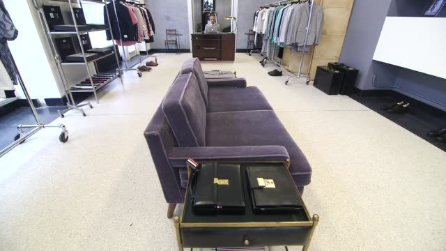 Various interior shots of the Thom Brown Retail Store in New York City New York A wide shot of a purple couch in the middle of the sales floor A wide...