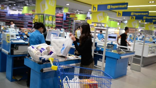 various medium and wide views of an employee scanning and bagging items from a customers purchase inside a hypermart supermarket, operated by pt... - plastic bag stock videos & royalty-free footage