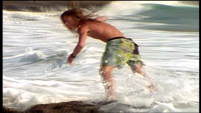 various men running into water and riding waves next to rocks in california - skimboard stock videos and b-roll footage
