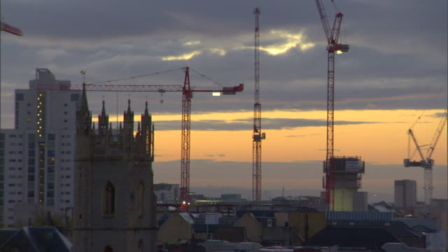 various mid high rise city buildings various construction cranes in distance cloudy sky bg uk - mid distance stock videos & royalty-free footage