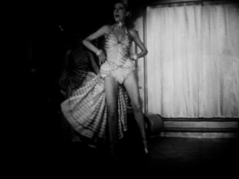various night clubs & lit neon signs. int vs tourists & people watching cabaret show, dancers on stage performing, guests drinking, band playing,... - 1950 video stock e b–roll