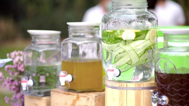 various of drink corner with infused detox water with cucumber and lemon, various healthy herbal juice in tank at outdoor wedding events. - detox stock videos & royalty-free footage